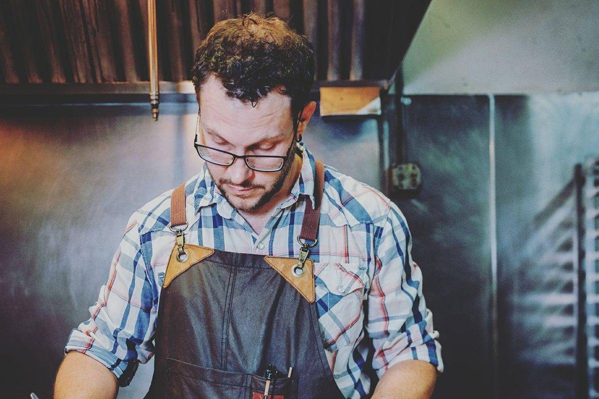 Jason Osburn wears a leather apron while plating a dish.