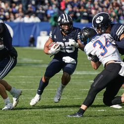 BYU running back Tyler Allgeier (25) runs past Boise State defenders for a touchdown during an NCAA college football game at LaVell Edwards Stadium in Provo on Saturday, Oct. 9, 2021.