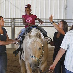 Clarissa Grove rides a horse as Andrea Smith, left, and Valerie Duffin help and Cindy Becker leads at the Buffalo Ranch in Farmington on Thursday. The therapeutic riding is organized by Becker's nonprofit group Therapeutic Assets.
