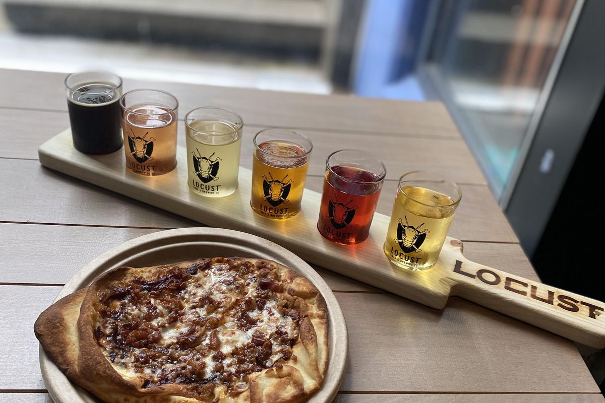 A wooden paddle with six cider tasters sits on a wooden table in the window at Locust's Vancouver taproom, sitting next to a cheesy flatbread pizza on a base of lightly-charred naan