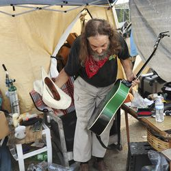 "Donald ""Hippie"" Montgomery takes a bow after playing his guitar at his tent at Camp Esperanza homeless camp in Austin, Texas, on Tuesday, Oct. 20, 2020."