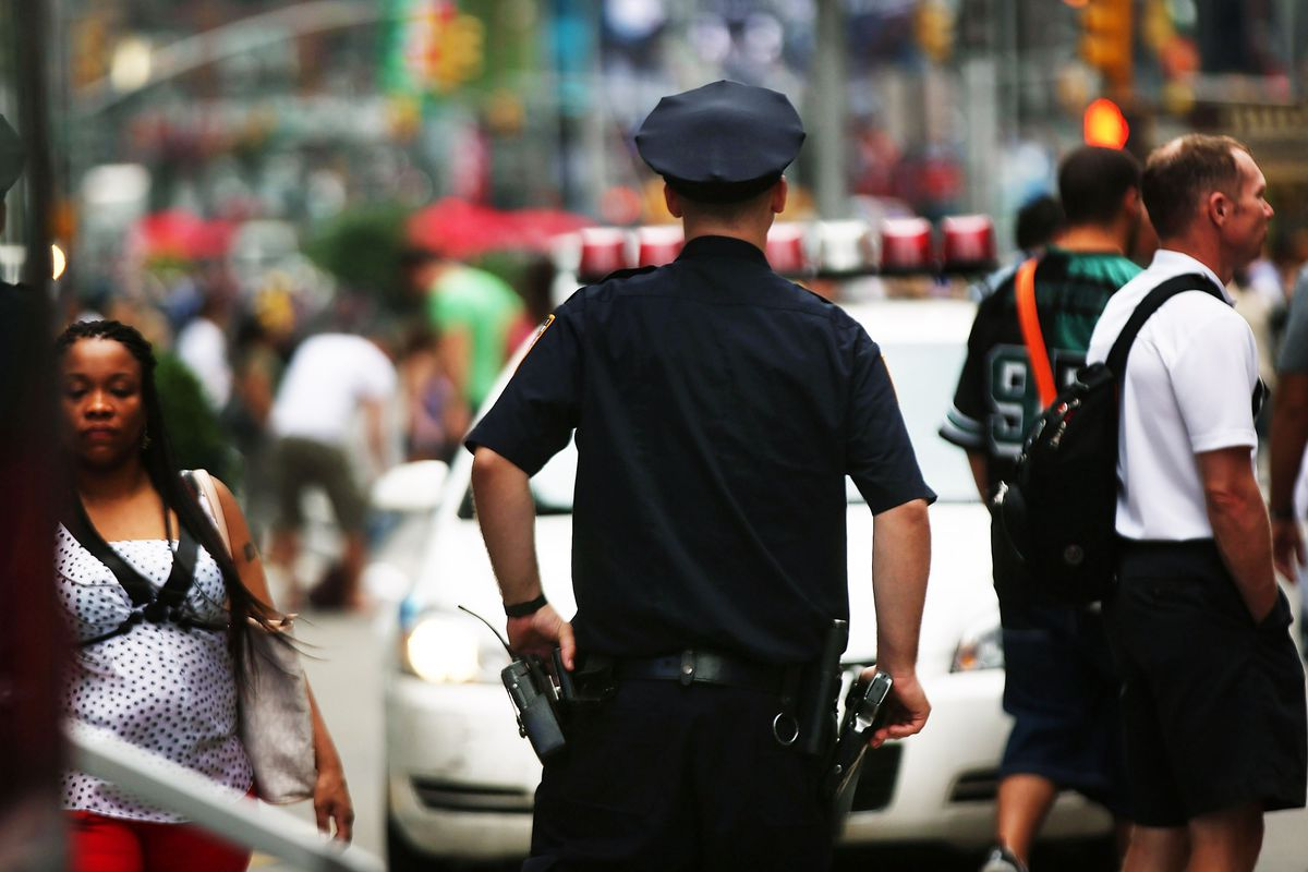 A New York City police officer watches over a crowd.