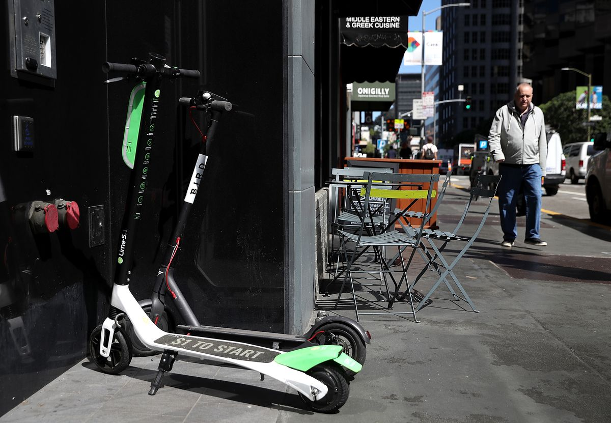 Green and white Lime scooters parked on the sidewalk. A male pedestrian walks near them.