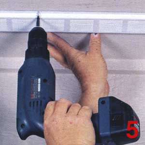 Person using a drill to install a soffit vent.