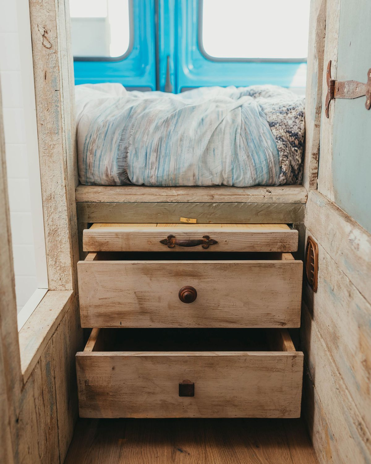 A photo of wooden drawers that pull out for storage underneath the bed. There's also a window to the left and the camper's blue doors in the rear.