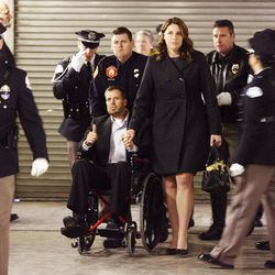 """Officer Shawn Grogan, one of the officers wounded in last weeks attacks, (chair) gives a """"thumbs up"""" as he is escorted by his wife Sandy and honor guard officers into the viewing prior to the funeral of officer Jared Francom at the Dee Events Center in Ogden Wednesday, January 11, 2012."""