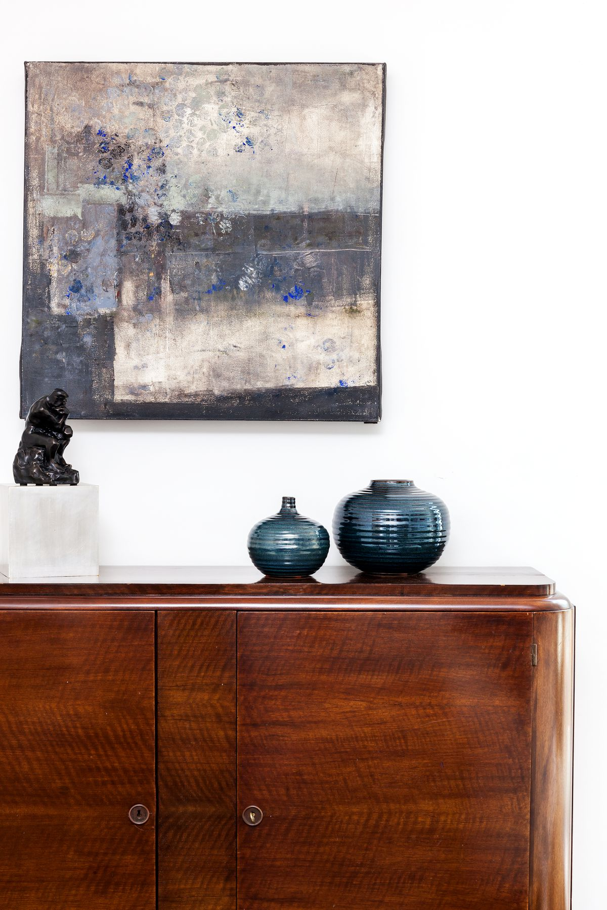 A brown antique cabinet is placed beneath an abstract painting.