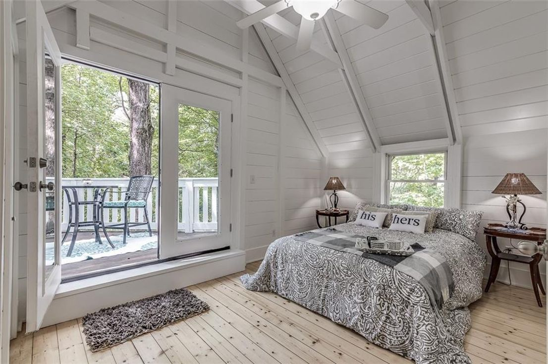 A white master bedroom with vaulted ceilings.