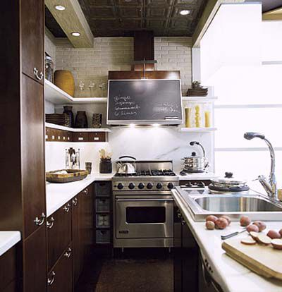 Shelving and drawers used in place of kitchen cabinets in a small kitchen.
