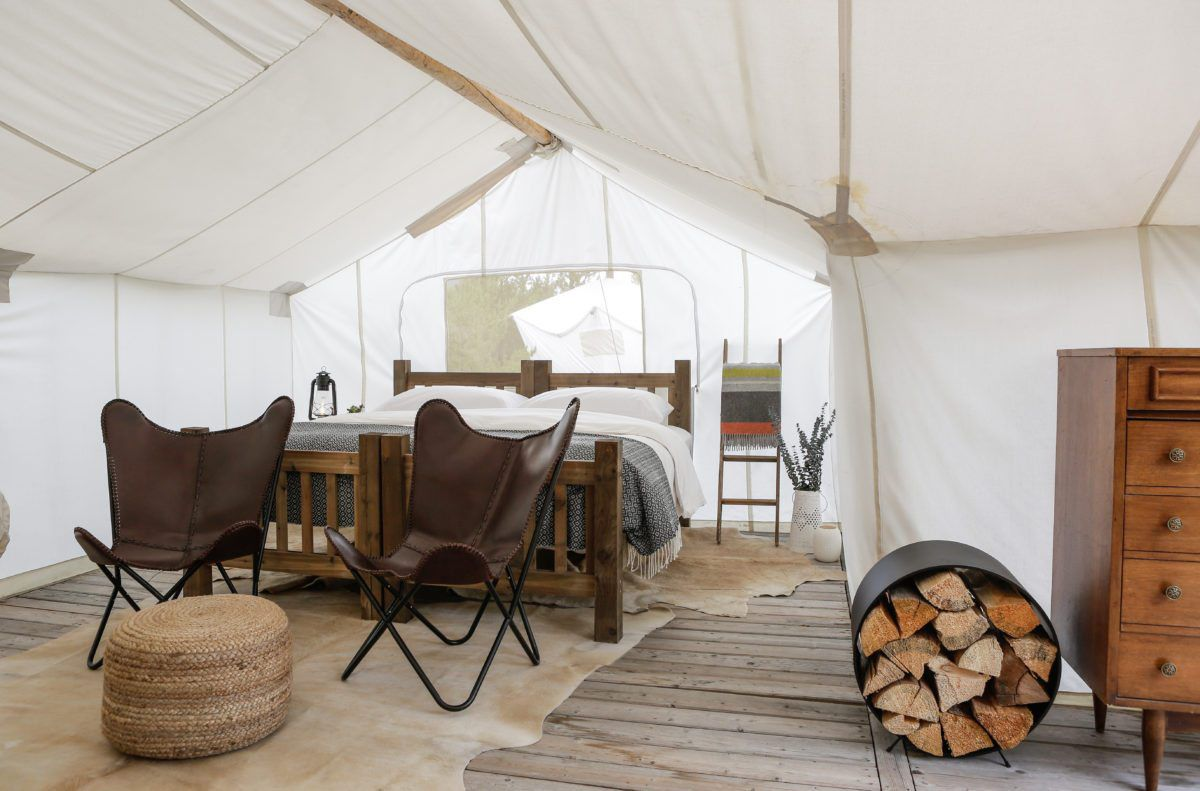 The inside of a glamping tent. There is a hardwood floor, chairs, a dresser, a large bed, and area rugs.