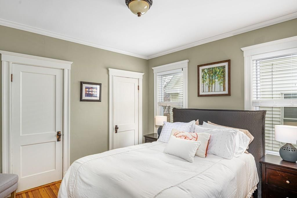 A bedroom with a bed and two closed doors, and two windows on either side of the bed.