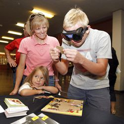 """Michael Atkinson, 15, tries to put together a simple puzzle while wearing """"Fatal Vision"""" goggles that simulate impairment from drinking while his mom, Patti Atkinson  and little sister Taylor Atkinson watch, during a driver safety program at Cottonwood High School, studies show that most children  learn driving habits from how  parents  do it, and studies show that's not necessarily a good thing, Wednesday, Sept. 19, 2012, in Murray, Utah."""