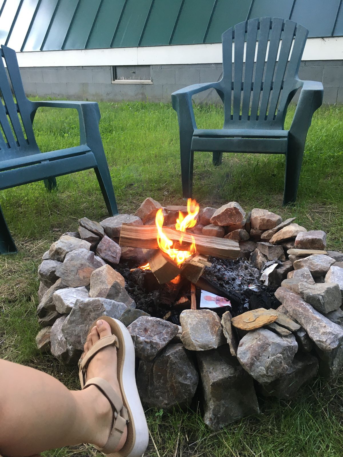 A campfire burns next to the cabin, with two chairs and the author's foot in view.