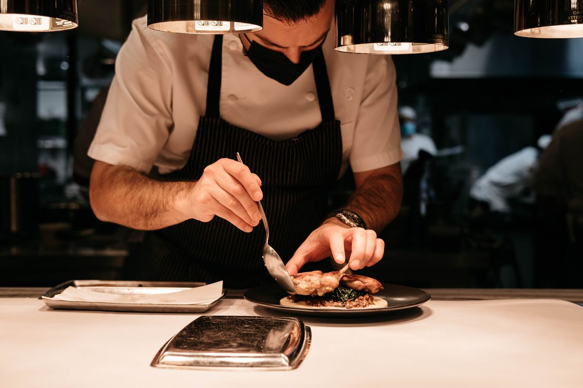 A man in a white shirt and black apron uses a spoon to place seared quail on a black plate.