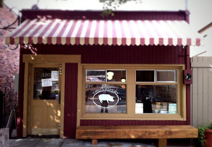 The storefront of The Swinery, with a candy-striped awning.