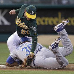 Kansas City Royals' Jason Bourgeois (30) is tagged out by Oakland Athletics third baseman Josh Donaldson (20) during the first inning of a baseball game Monday, April 9, 2012, in Oakland, Calif. Bourgeois was attempting to advance on a sacrifice fly hit by Lorenzo Cain.