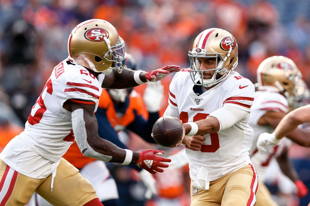 San Francisco 49ers quarterback Jimmy Garoppolo hands the ball off to running back Tevin Coleman in the first quarter against the Denver Broncos at Broncos Stadium at Mile High.