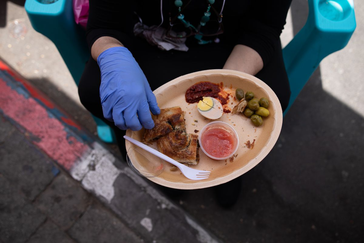 A woman uses a glove to eat a dish from Levinsky Burekas, while sitting on a plastic chair at a section of Levinsky market that was converted into a pedestrian street in Tel Aviv, Israel, June 02, 2020.