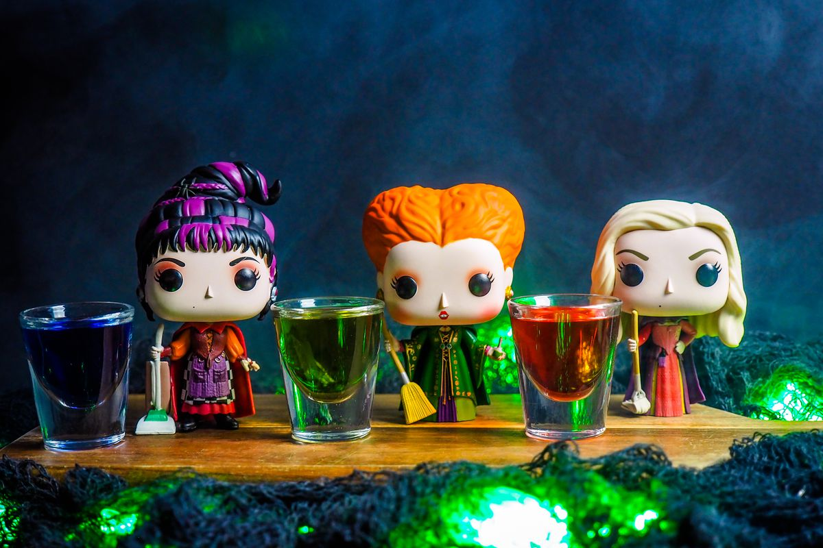 Three figurines of the Sanderson sisters stand beside filled shot glasses