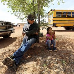 Bobby Benally and his granddaughter, Sophie Hunt, sit outside of their home in Halchita, San Juan County, which is part of theNavajo Nation, on Friday, April 17, 2020. The Navajo Nation has one of the highest per capita COVID-19 infection rates in the country. Benally and Hunt are asymptomatic but got tested earlier in the day to be safe.