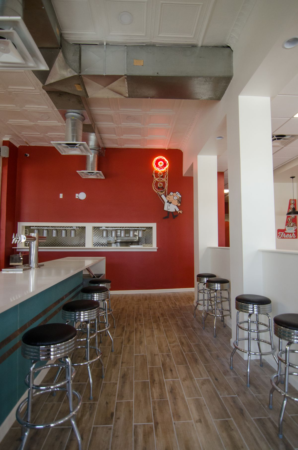 Interior view of a diner with stools lining a counter with teal accents. A bright red wall is in the back with neon signage depicting a diner cook holding a stack of doughnuts.