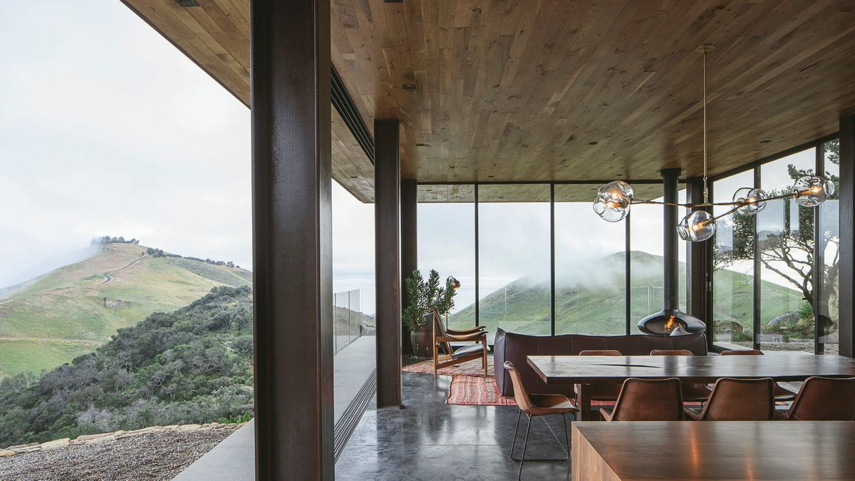 Interior of house with large windows looking out onto rolling hills