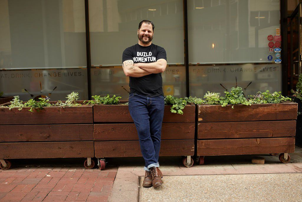 """Chef Chad Houser stands in front of wooden planter boxes, wearing a black t-shirt that reads """"Build Momentum,"""" jeans, and brown shoes."""