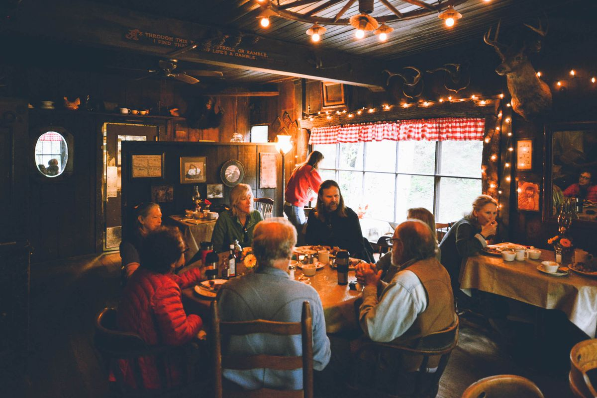 Cold Spring Tavern's woodsy interior dining room, with lob cabin vibes. A table of diners gather together under a low lamp.
