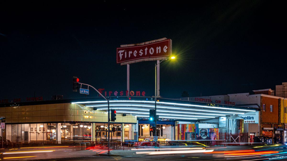 A retro streamline moderne former car dealership redone as a bar, shown at night.