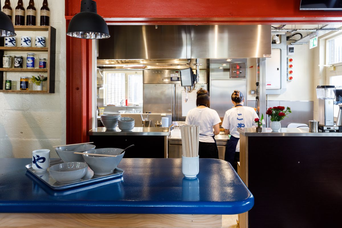 In the foreground, a denim-blue counter, stacked with chopsticks, udon bowls, and cups. In the background, and open kitchen, with two chefs, whose backs are to the camera.