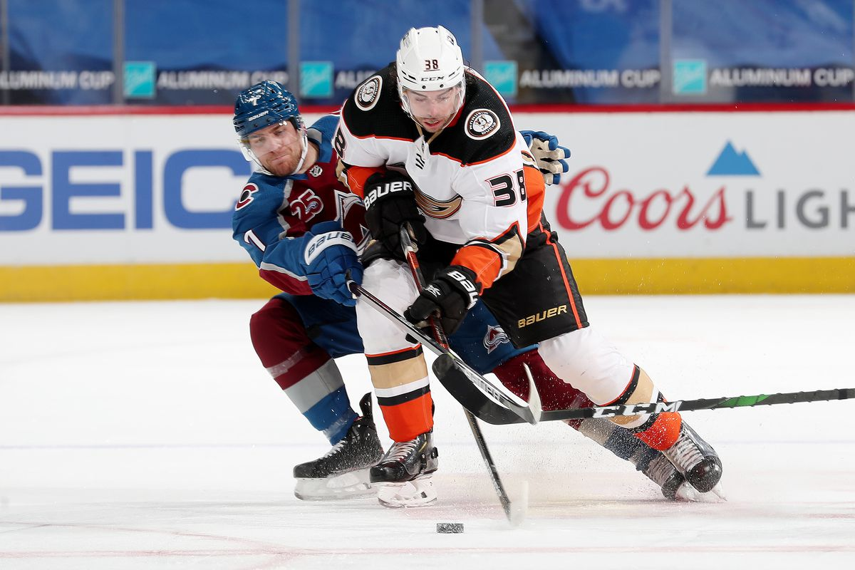 Derek Grant #38 of the Anaheim Ducks battles for position against Devon Toews #7 of the Colorado Avalanche at Ball Arena on March 29, 2021 in Denver, Colorado.