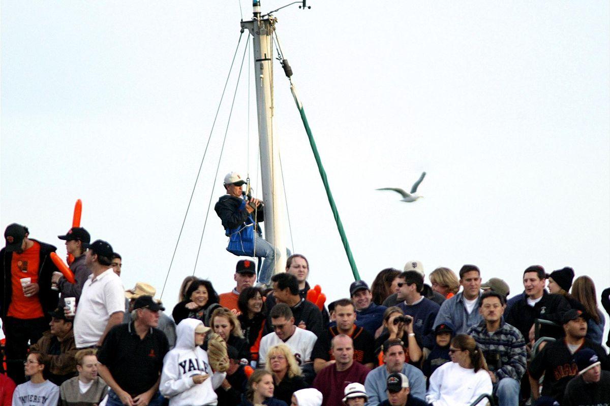 A fan (C back) who climbed up a sailboat mast gets