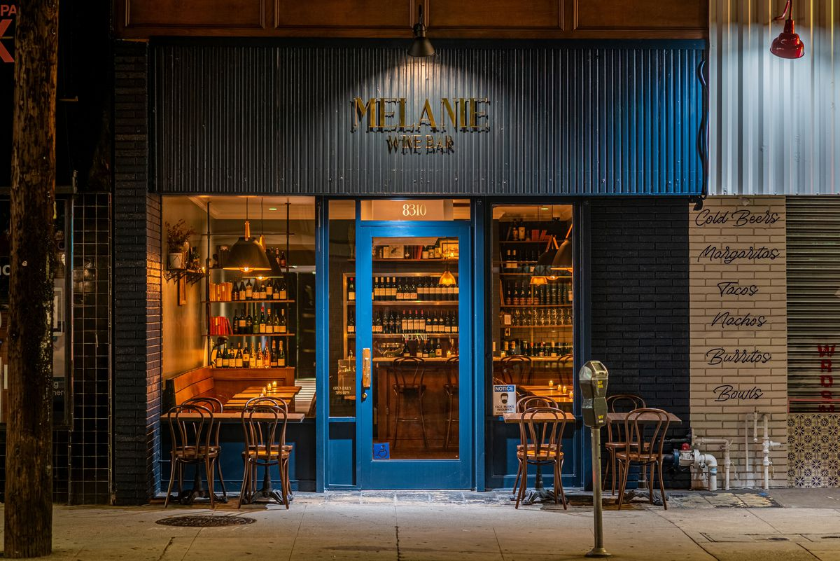An evening glow from inside of a wine bar with a dark blue exterior and some outside tables.