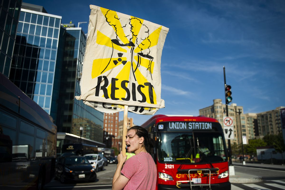 "A climate change protester holds up a sign showing nuclear reactors and the word, ""Resist."""