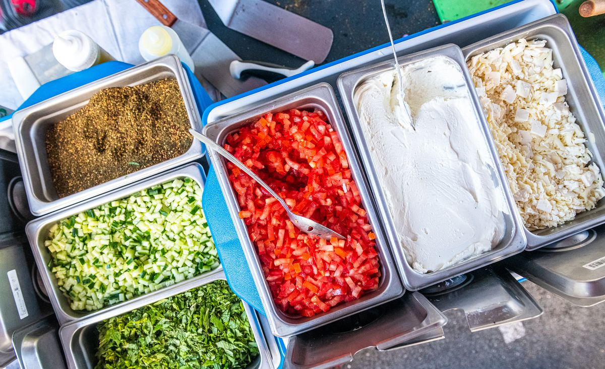 An overhead shot of metal containers filled with za'atar, cucumbers, tomatoes, labneh, and cheese for Z&Z's manoushe
