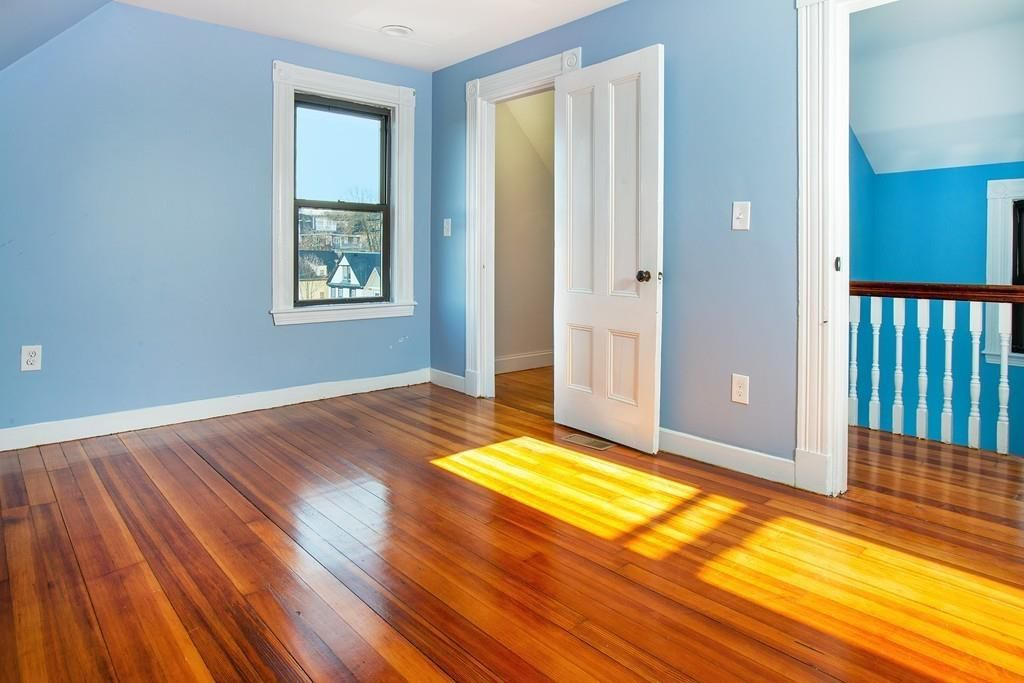 An empty room off some stairs with a window and an open closet door.