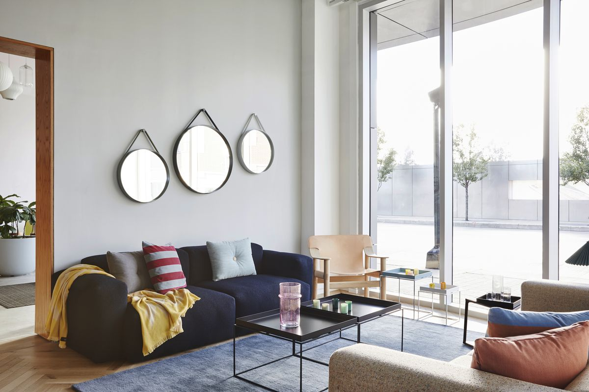 A showroom with large windows, circular hanging mirrors, sofas, and tables.