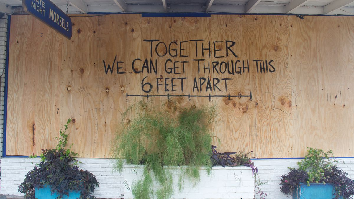 """Ah Sing Den's boarded-up windows with the message of """"Together We Can Get Through This 6 Feet Apart"""""""