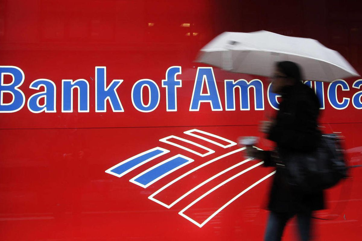 In this Dec. 7, 2011 file photo, a woman passes a Bank of America office branch, in New York. Bank of America said Friday, Sept. 28, 2012 that it has agreed to pay $2.43 billion to settle a class-action lawsuit related to its acquisition of Merrill Lynch