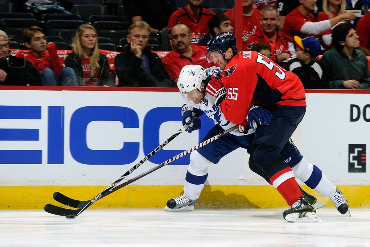 WASHINGTON, DC - OCTOBER 10:  Jeff Schultz #55 of the Washington Capitals battles for the puck with Dominic Moore #19 of the Tampa Bay Lightning at the Verizon Center on October 10, 2011 in Washington, DC.  (Photo by Greg Fiume/Getty Images)