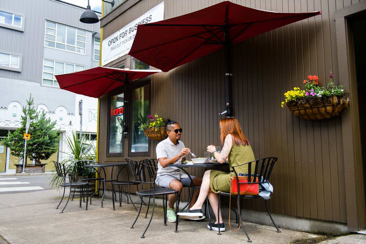 A couple sits at a metal table outside Fuel Cafe, eating breakfast and drinking coffee. Every other table is empty.