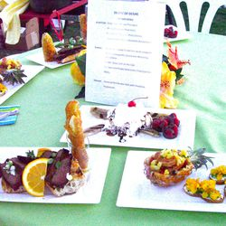 """The winning dishes from the Iron Pig Championship Cook-Off: A """"shrimp boat"""" served in a baby South African pineapple, a crostini topped with edible flowers, a sandwich of Pacific-rim glazed tenderloin steak, spicy corn on the cob, zucchini sticks, and a honey-grilled banana split. (Valerie Phillips)"""