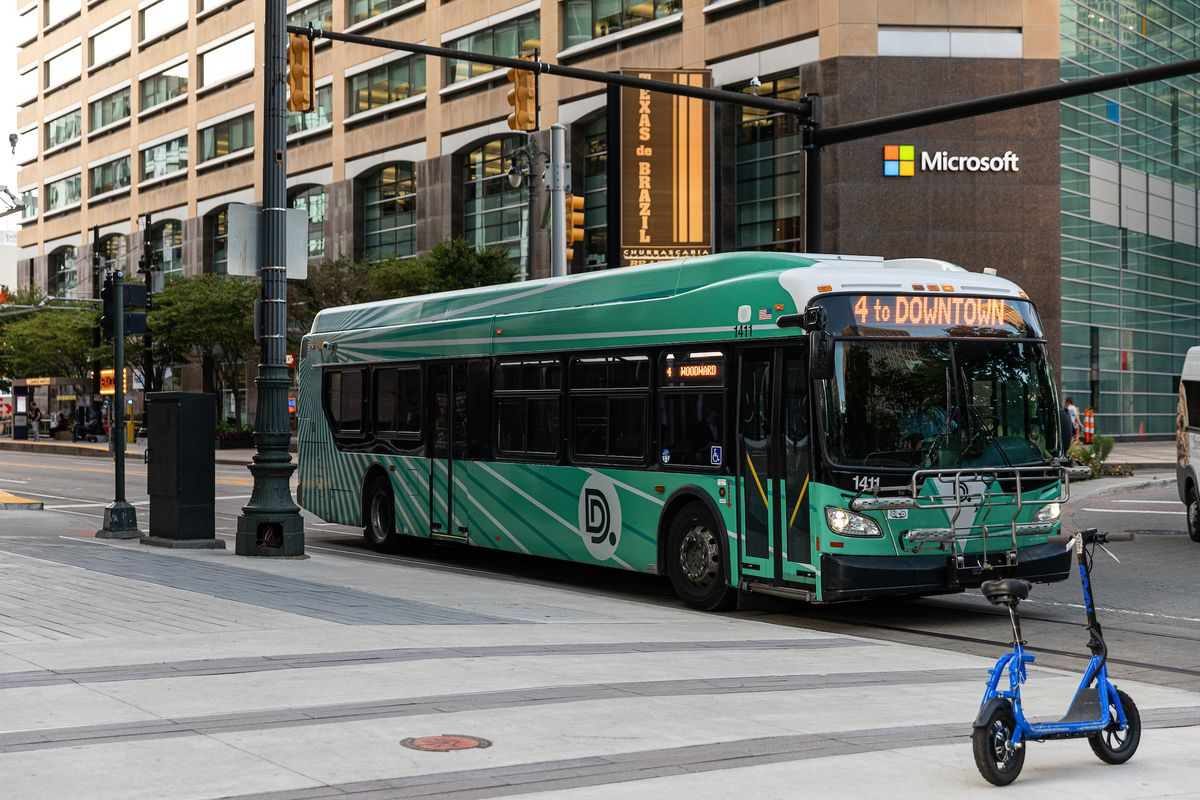 A green and white bus in front of a large office building.