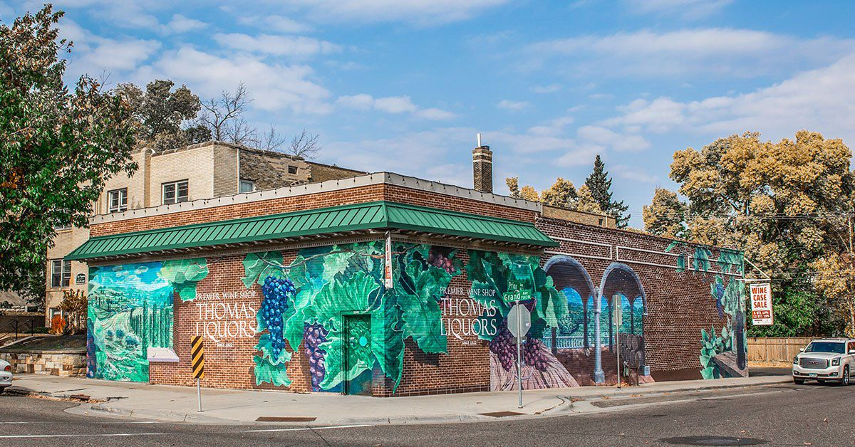 The brick exterior of the small building is covered in a grape and grape leaves mural