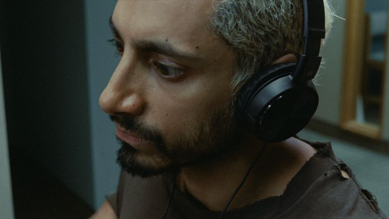 A close-up of Riz Ahmed's face as he wears headphones.