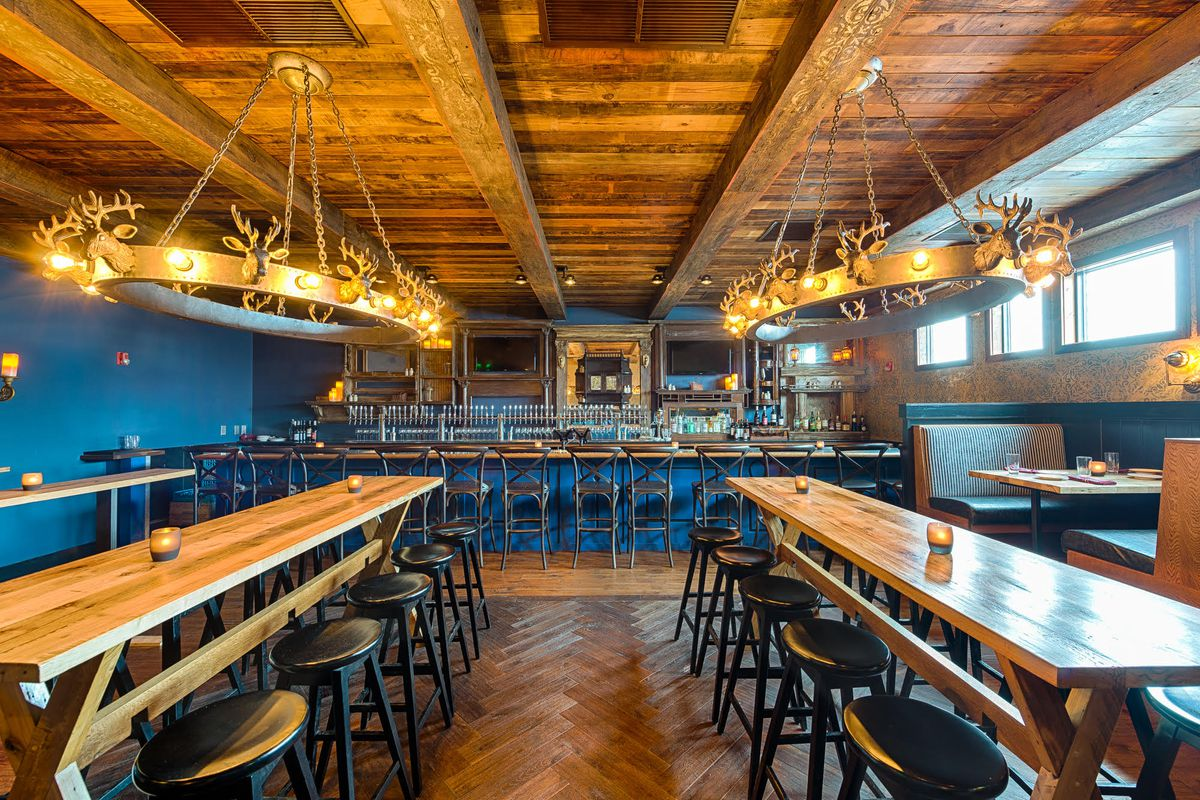 Two rows of wooden tables with bar stools, lit by two dramatic chandeliers falling from a wood paneled ceiling