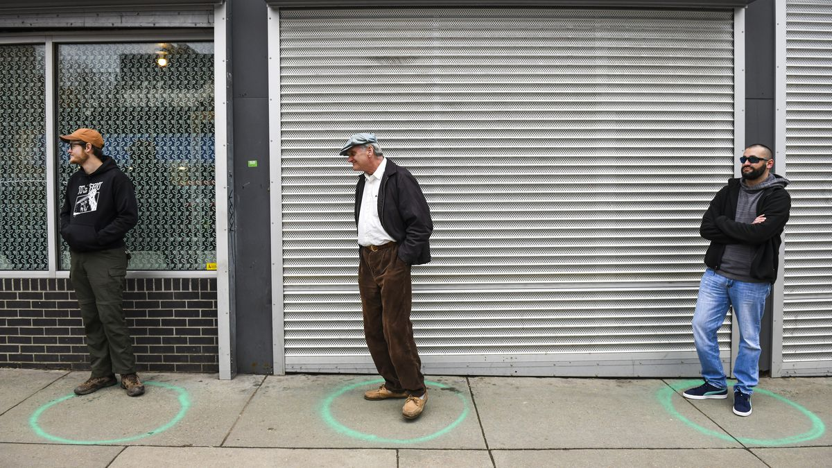 Residents of Denver practice social distancing while purchasing essentials at a local store.