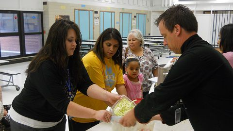 Parent Regina Hurtado works with a nutrition services staff member to package cabbage during a cooking class at Rose Hill Elementary School in Commerce City.