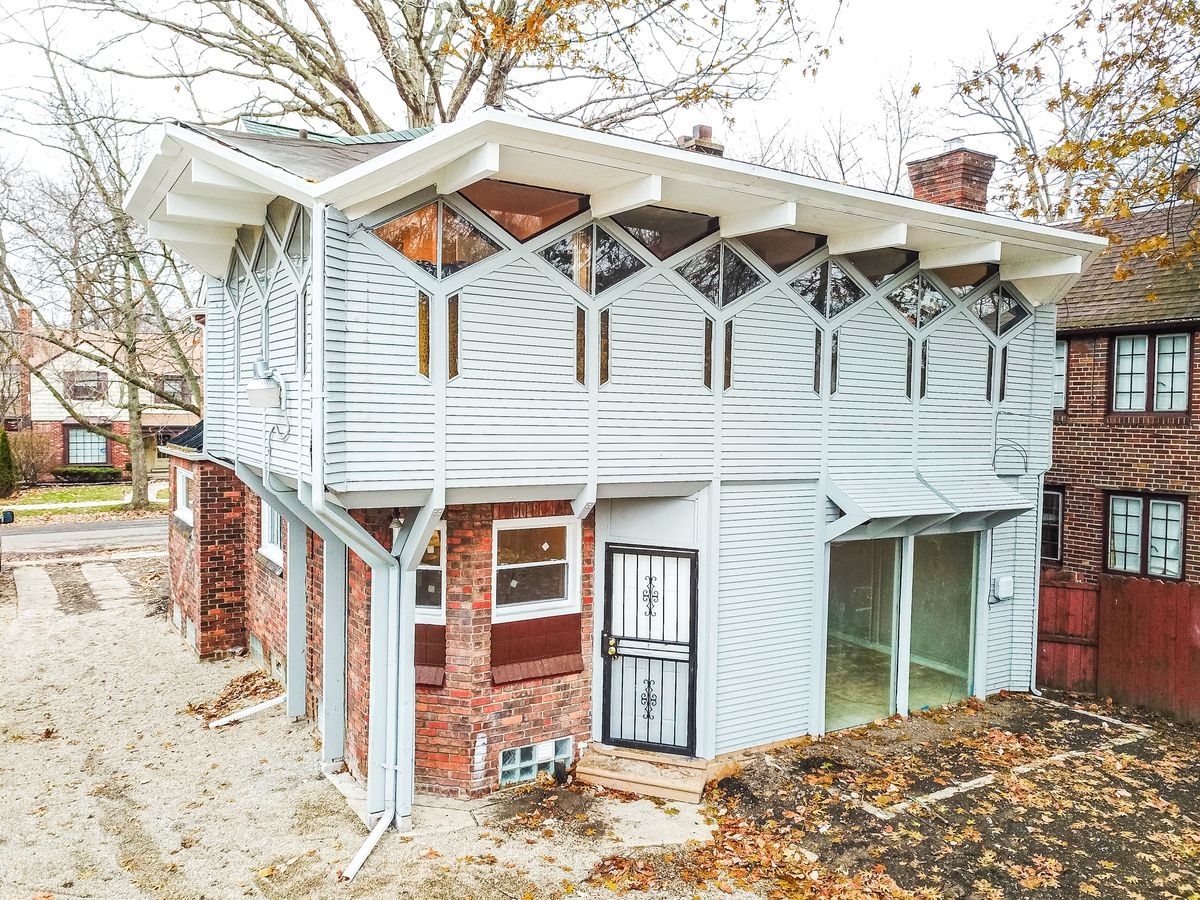 White vinyl siding attached to the brick house that spans two floors. The diamond windows run along the wall near the roof.