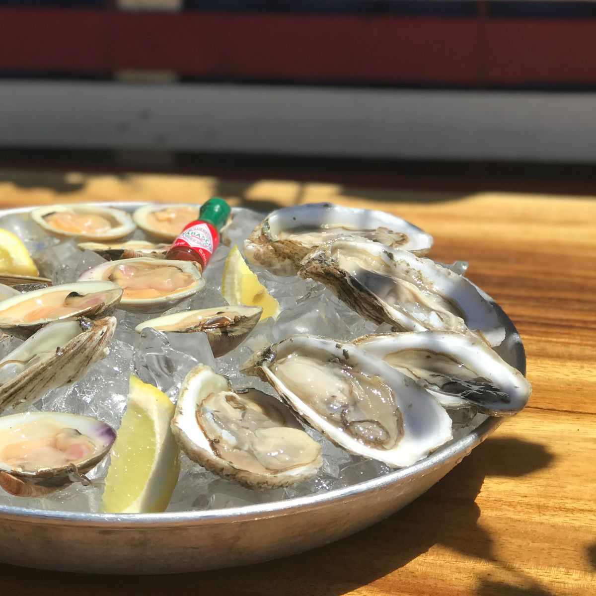A bowl of ice topped with oysters in their shell with a bottle of tobasco sauce in the middle